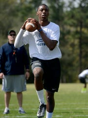 University of West Florida quarterback Tyrone Jones throws some warmup passes Wednesday as practice gets under way for the currently enrolled players. The practice was the first of five dates for the spring semester.