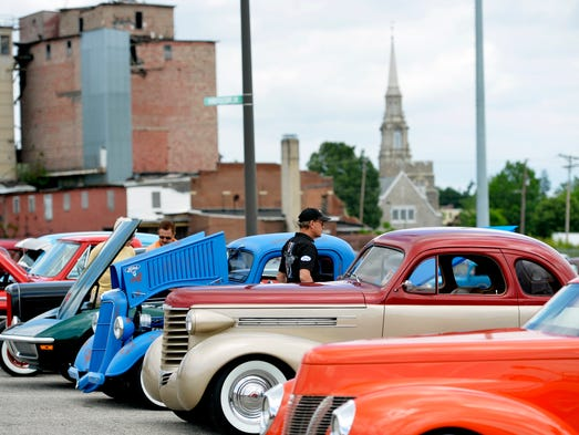 People walk around street rods parked at the 42nd annual