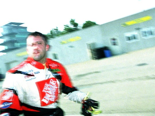 Driver Tony Stewart walks through the garage area at