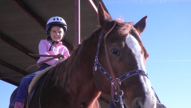 A young rider in the New Mexico State University Therapeutic Riding Program appears on horseback.