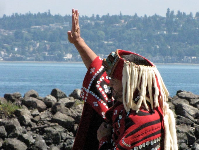 A greeter in the traditional Kwakiutl button blanket welcomes dinner guests off the boat from Seattle.