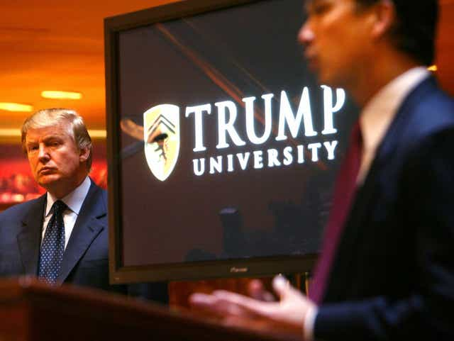 Donald Trump listens as Michael Sexton (R) introduces him to announce the establishment of Trump University at a press conference in New York.