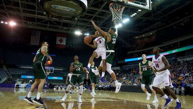 University of Evansville's Ryan Taylor (0) goes for a layup as Binghamton's University's Thomas Bruce (32) defends him at the Ford Center in Evansville, Ind., on Saturday, Nov. 18, 2017.