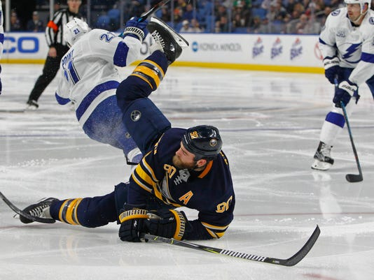 Buffalo Sabres forward Ryan O'Reilly (90) falls to the ice after a collision with Tampa Bay Lightning forwrad Brayden Point (21) during the second period of an NHL hockey game, Tuesday, Feb. 13, 2018, in Buffalo, N.Y. (AP Photo/Jeffrey T. Barnes)