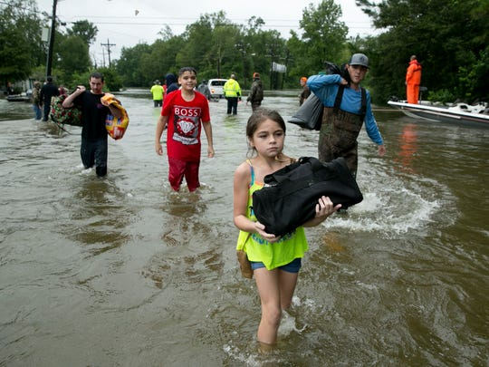 Jaylen Welch, 10, carries her belongings out of the flood on Tram Road after being rescued from flooding by boat from her home in Beaumont, Texas.
