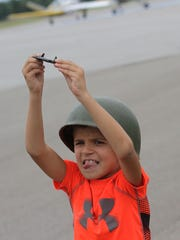 Ethan Line, 8, plays with his toy airplane during the