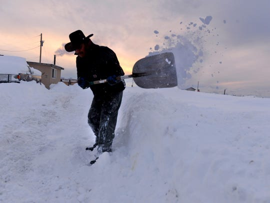 Jeff Wooden Legs shovels his driveway on Tuesday evening