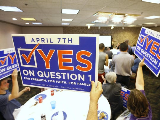 Supporters of Yes on Question 1 hold up signs during