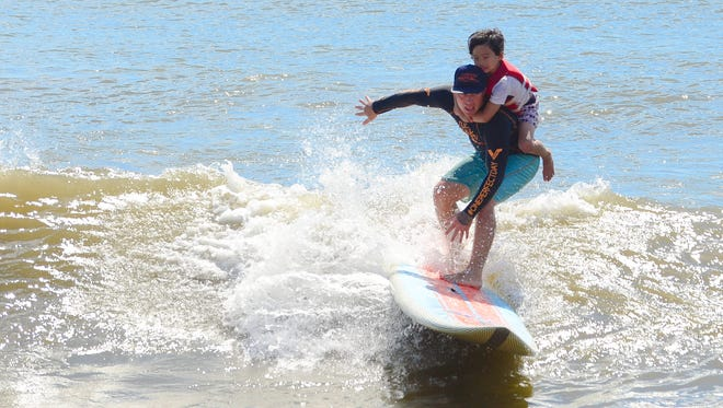 Aides Malacas, Balitmore, Md. gets assistance from a volunteer with the Surfers healing tour catch a wave in Ocean City. on August 17, 2016.