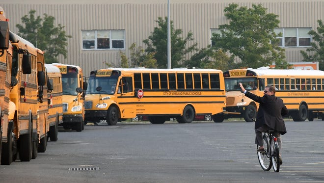 Vineland High School principal Dr. Tom McCann waves to the students while they're on bus at the 1st day of school.  Sept.  3, 2015.  Staff photo/Craig Matthews