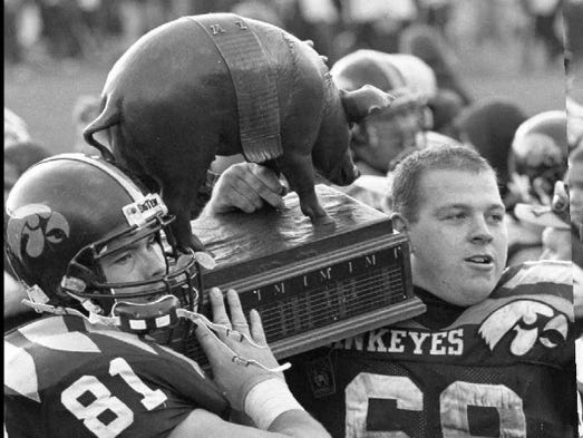 Chris Knipper (81) and Jeremy McKinney of Iowa carry off Floyd of Rosedale, the spoils of the Hawkeyes' 45-3 victory over Minnesota.