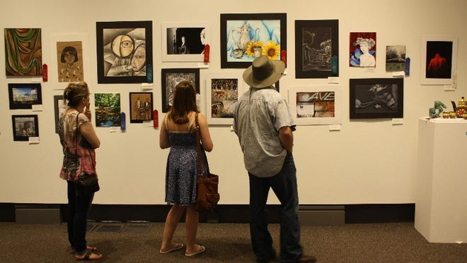 :  Student artist Allyson Ayres, 18, center, views part of the exhibit with her parents Kathy and Travis Ayres during the opening day of the 44th Annual New Albany-Floyd County Secondary Schools Art Show and Competition at the Carnegie Center for Art & History in New Albany on Saturday.