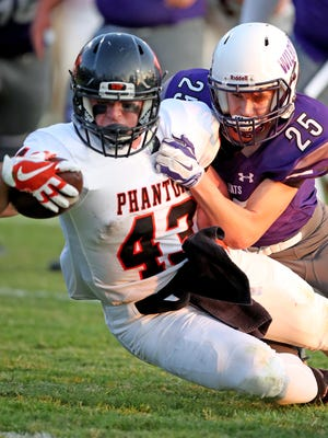 West De Pere running back Austin Beaumier scores despite the tackle of  West Wildcats' Kade Olson Friday September 1, 2017 at West High School in Green Bay, Wis.