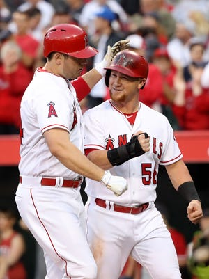 C.J. Cron of the Los Angeles Angels of Anaheim is congratulated by Kole Calhoun after hitting a two-run home run during the first  inning.