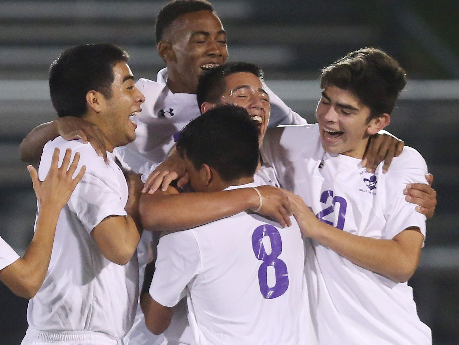 New Rochelle's Oscar Espinoza (13) celebrates with teammates after scoring New Rochelle's first goal against Ithaca during the boys soccer regional semifinal at Lakeland High School in Shrub Oak Nov. 2, 2016