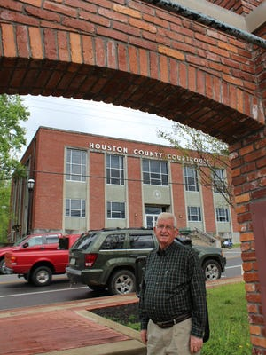 "Houston County Mayor George ""G.E."" Clark poses among the remnants of the old courthouse in front of the new courthouse."
