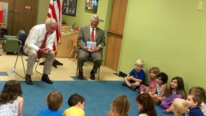 Maj. Gen. (Ret.) Michael Davidson, left, and Maj. Gen. (Ret.) Robert Silverthorn of Louisville talk to preschoolers about the flag June 24 at Bright Horizons childhood center, 632 S. Fourth St.
