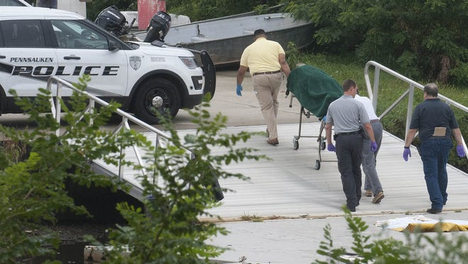 Police wheel a body away from the Cooper River, where it was found Thursday morning.