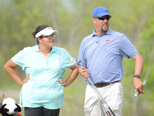 Cooper sophomore Sarah Aitchison listens to Lady Cougars' golf coach Bryan Bruning during the team's practice April 12 at Diamondback Golf Club.