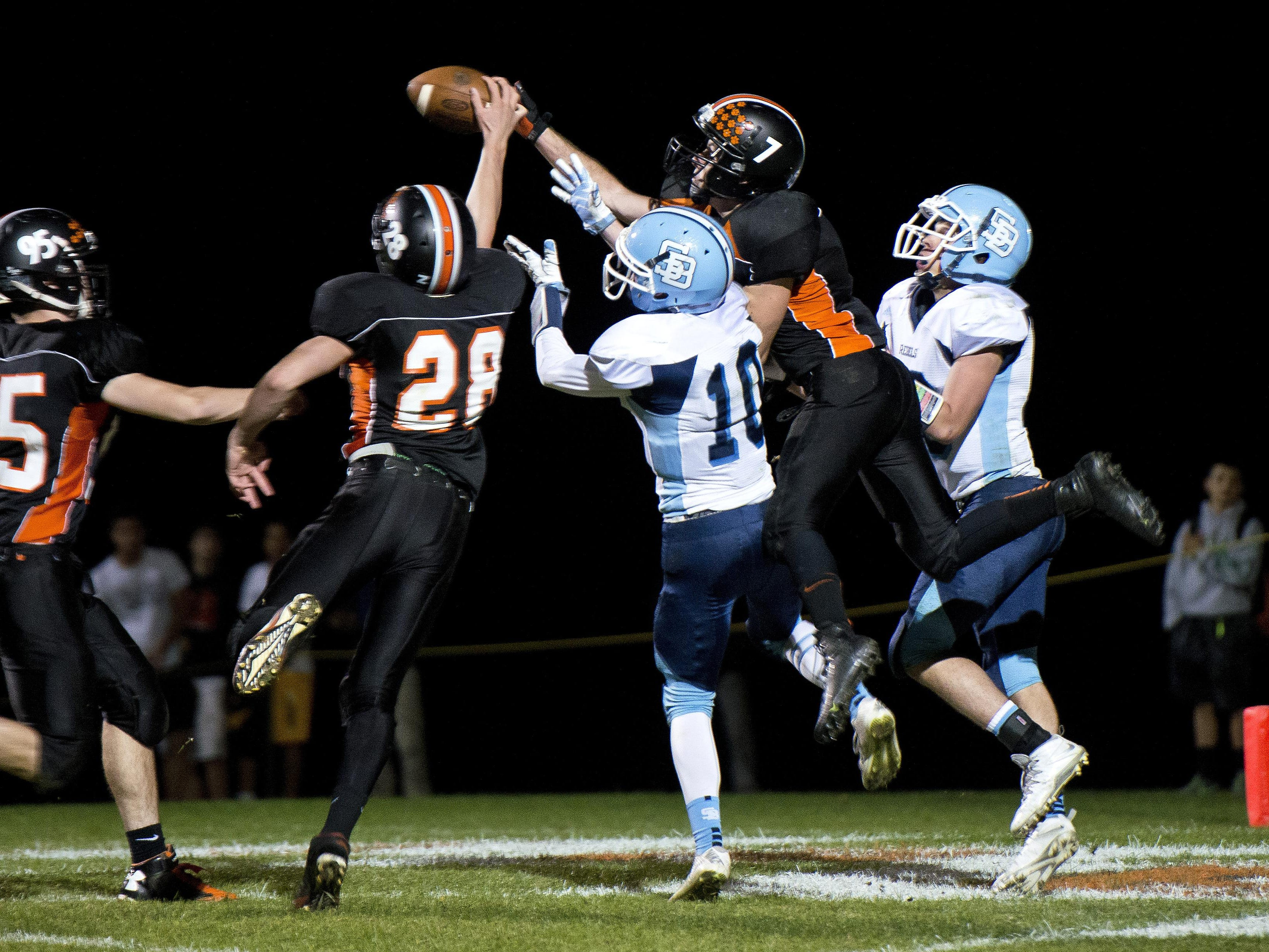 Middlebury's Oakley Gordon (7) and Jerry Niemo (28) break up a South Burlington pass in the end zone during Friday night's football game in Middlebury.