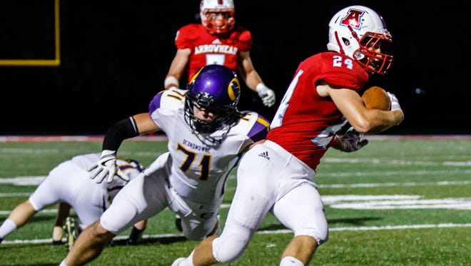 Arrowhead senior Carter Bell (24) races up the sideline with Oconomowoc's Jackson Sussek (71) giving chase during the game at Arrowhead on Friday, Sept. 22, 2017.