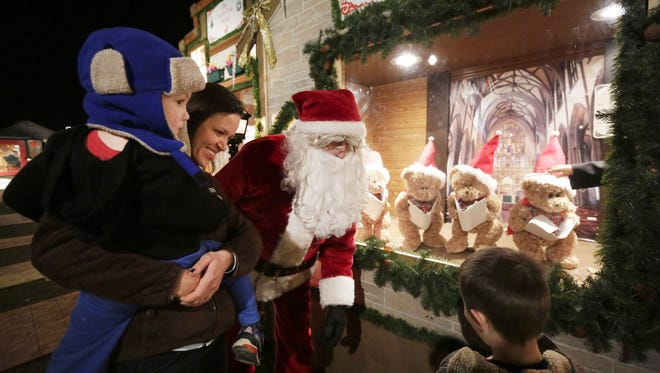 Troy Campbell, dressed as Santa, welcomes Jenna Linden and her sons, Ellis and Lucas (right), to 830 Rusty Court in Kaukauna, where his elaborate display of Christmas lights draws a crowd.