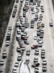 In this aerial photo, abandoned cars at I-75  headed northbound near the Chattahoochee River overpass are piled up in the median of the ice-covered interstate after a winter snow storm  on Jan. 29 in Atlanta.