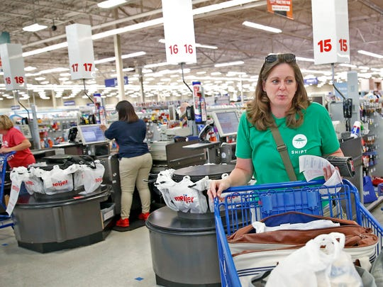 Joelee Smith, with Shipt, shops for groceries for local company, at the 96th St. Meijer, Thursday, June 29, 2017.  Meijer customers place orders through a Shipt app and their shoppers do the shopping and delivery.  Smith and other shoppers wait in line and check out just like other customers.