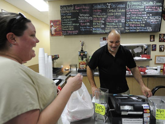 Brad Carr, right, jokes around with a customer in his
