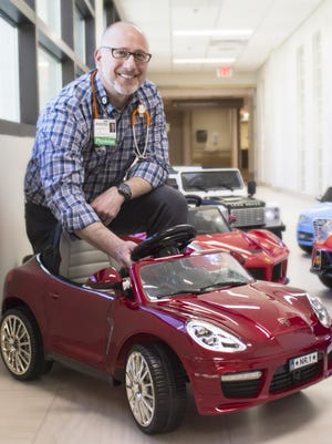 Dr. Jeffrey Schwartz, pediatric hematologist/oncologist and medical director of the University of Florida pediatric specialists at The Studer Family Children's Hospital at Sacred Heart, poses with the red Porsche he donated.