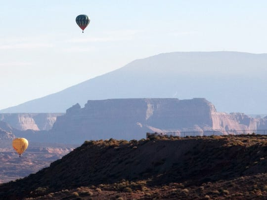 Hot air balloons float throughout he skies while Tower Butte and Navajo Mountain stand in the background as they drift east on the early morning winds Sunday, Nov. 3, 2013 in Page, AZ..