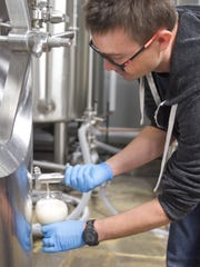 Aberrant Ales head brewer Adam Stout checks a sample