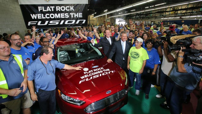 Workers surround a 2014 Ford Fusion which ceremoniously was rolled off the line at the Flat Rock Assembly Plant in Flat Rock, Michigan on Thursday, August 29, 2013.