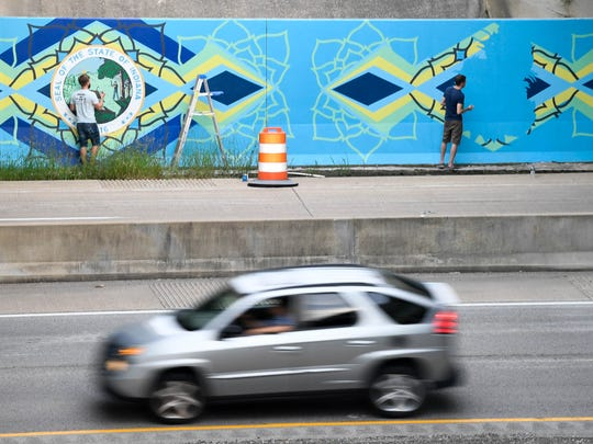 MIKE LAWRENCE / COURIER & PRESSWith traffic constantly whizzing by artists Matt Fitzpatrick (left) and Jon Whitman work on a 9 feet tall and 75 feet wide mural he designed under the I-69 and U.S. 41 overpass recently, July 28, 2016.