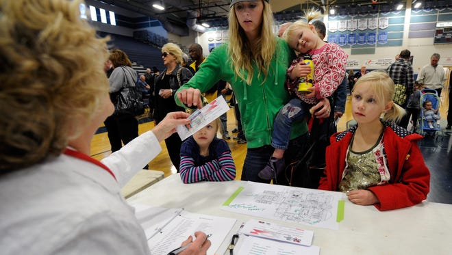 LAS VEGAS, NV - FEBRUARY 04:  A caucus worker checks in Katherine Wood with her three daughters (L-R) Ellie Wood, Reese Wood and Ashlyn Wood before the start of the Republican caucus at Centennial High School on February 4, 2012 in Las Vegas, Nevada. Nevada is the first state in the West to vote as Republicans go about choosing their presidential candidate.  (Photo by David Becker/Getty Images)