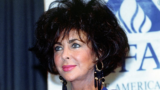 """British-born American actress Elizabeth Taylor at an auction to benefit the American Foundation for AIDS Research in Beverly Hills on June 3, 1991. """"Glitter and Be Giving"""" will be two events of fine jewelry auctions and dinner dances to benefit AmFar in Beverly Hills in the fall of 1991 and New York in the spring of 1992. Taylor is Honorary Chairman of the Auctions. (AP Photo/Ed Bailey)"""