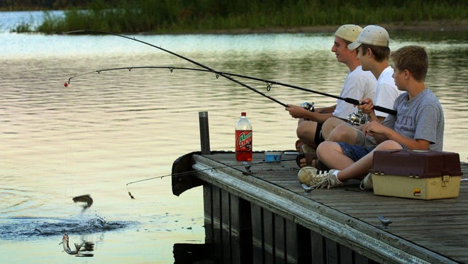 - -Photo_By: JOHN GAPS III/THE REGISTER- - Andrew Locasha, 14, right, and Aaron Anderson, 16, left, simultaneously catch two catfish as David Locasha, 16, looks on Sunday evening at the Raccoon River Park dock in West Des Moines. All three are from West Des Moines.