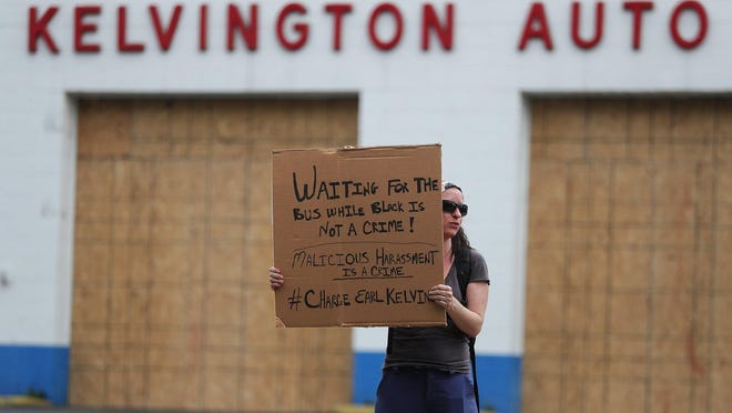 Faith Wally of Ellet protests Wednesday outside Kelvington Auto Service in Akron. The white owner of the auto shop is accused of bringing a shotgun to confront a black man at a bus stop.