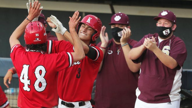 Kent Roosevelt's Zach Holman (48) is welcomed back to the dugout by Zac Common (3) after scoring during the fourth inning Saturday, July 25, 2020, at Canal Park in Akron, Ohio.