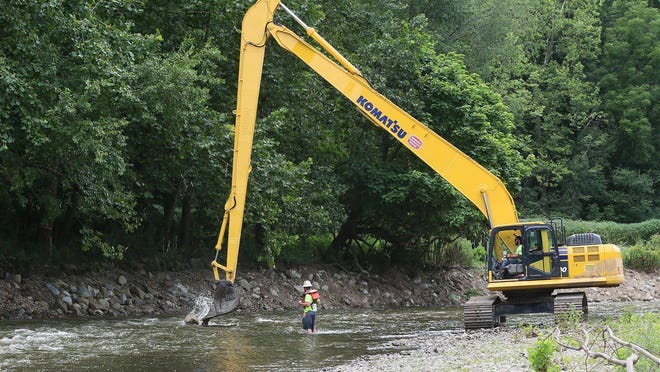 RiverReach Construction worker Chase Guello uses an excavator to drop a boulder in place in the Cuyahoga River under the direction of Broc Benner as they make in-stream habitat improvements for fish and aquatic wildlife at the former Valley View Golf Club on Monday, July 20, 2020, in Akron.