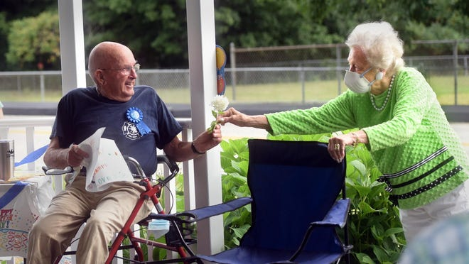 Gladys Butterworth hands birthday boy Orland McPherson a freshly picked flower on his 90th birtday at the town gazebo. The two went to high school together and were dance partners, she recalled.