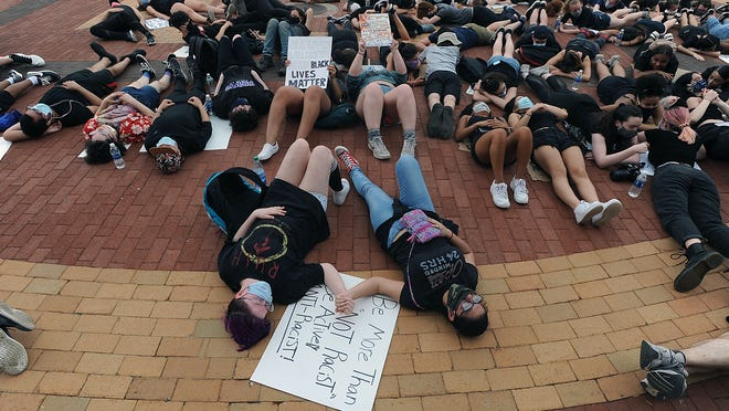 Participants lay down for nine minutes Wednesday at a Black Lives Matter march and rally in front of the steps of city hall in downtown Framingham.