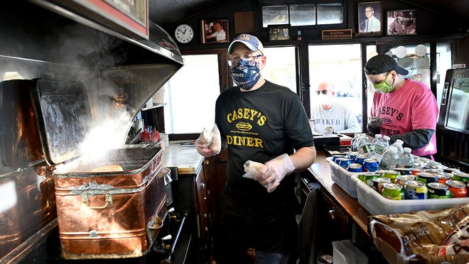 Patrick Casey, the fourth-generation owner of Casey's Diner in downtown Natick, works inside the tiny diner on Thursday, Nov. 5, 2020. Due to the coronavirus pandemic, indoor seating in the tiny eatery is not possible but the business carries on with window and curbside service as well as outdoor seating.