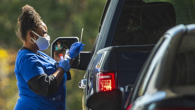 A health care worker administers a COVID-19 test in a drive-thru testing area at Family Emergency Room in Cedar Park on Nov. 11.