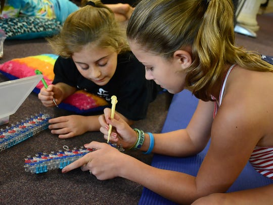 Madison Bates, 9, and Jade Wheeler, 11, concentrate on making loom bracelets for local veterans.
