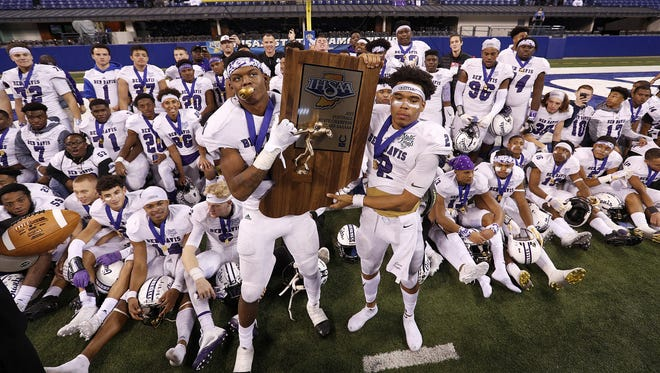 Ben Davis players show off the Class 6A state title trophy at Lucas Oil Stadium this past November.