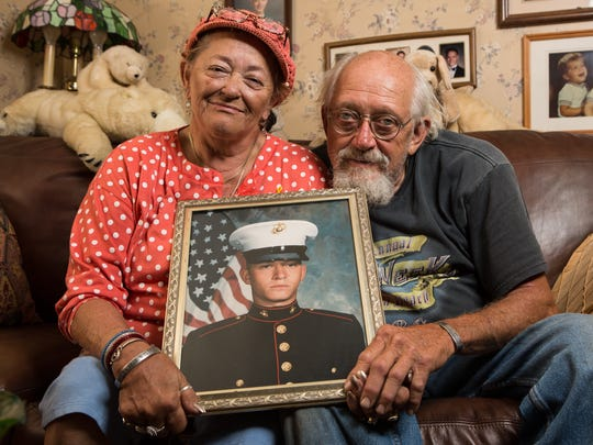 "Jeanne and Walter Cohee II pose for a photo holding a picture of their son Walter ""Trae"" at their Mardela Springs home on Monday, May 22, 2017. The 26-year-old Marine was Maryland's first death from the war in Afghanistan."