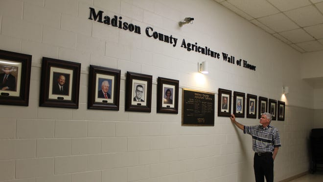 Kevin Perry, the agency manager for the Madison County Farm Bureau, stands in front of the 'Madison County Agricultural Wall of Honor.' Members of the Madison County Farm Bureau will place three new honorees on the wall this week.