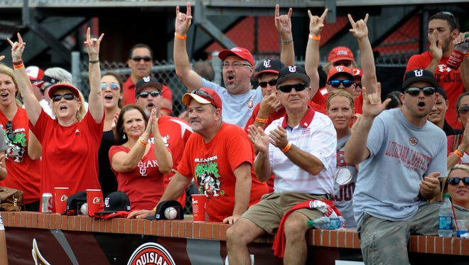 UL baseball fans standing down the leftfield line react to receiving a sixth overall seed in the NCAA Baseball Selection Show program Monday while watching it on the scoreboard at Tigue Moore Field.