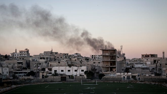 Smoke rises after a mortar shell hits a residential area during fighting between Syrian government forces and rebels in Maaret al-Numan in the Idlib province, Syria, on Oct. 9, 2013.